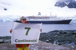 Ecological tourist from cruise ship Marco Polo with Seven Continents sign at Paradise Harbor, Antarctica Royalty Free Stock Photography
