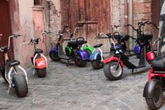 Ecological transport for tourist excursions. Many electric scooters with keys in the old courtyard of the old blurred city. Rent of electric transport for stock photos