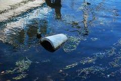 Ecologisch probleem Vuilnis in het water De plastic flessen verontreinigen aard Flessen en huisvuil in de haven van zeehaven van  stock foto