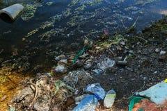 Ecologisch probleem Vuilnis in het water De plastic flessen verontreinigen aard Flessen en huisvuil in de haven van zeehaven van  royalty-vrije stock fotografie
