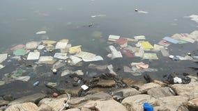 ecologische crisisfoto Plastic flessen, zakken, afval in rivier of meer Vuilnis en verontreiniging die in water drijven motie stock video