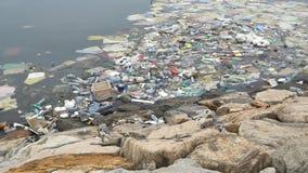 ecologische crisisfoto Plastic flessen, zakken, afval in rivier of meer Vuilnis en verontreiniging die in water drijven motie stock footage