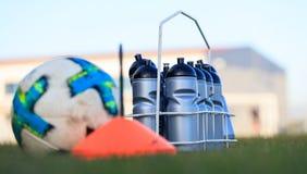 Ecologische sportflessen zoet water op het gras van het voetbalgebied Vage voetbalbal en kegel royalty-vrije stock fotografie
