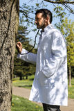 Ecologist. Young doctor with stethoscope in a park Stock Photos