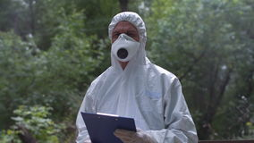 Ecologist with file. Anonymous biologist in protective suit holding file and looking at camera on background of nature stock video footage
