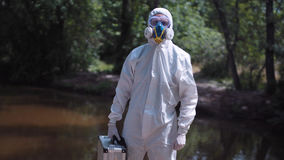 Ecologist with file. Portrait of anonymous biologist in protective suit holding file and looking at camera on background of nature royalty free stock photography