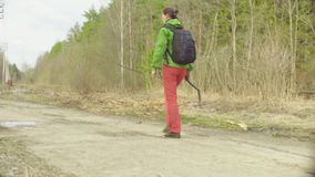 The ecologist going to the place of research. The scientist ecologist going to the place of research on the forest road at spring day stock footage