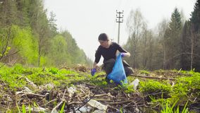 The ecologist going to the place of research. The woman ecologist collecting garbage in a garbage bag in the forest stock video footage