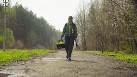 The ecologist going to the place of research. The woman ecologist going to the place of research on the forest road at spring day stock footage