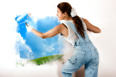 Ecologist Mural Painting on Wall. Young woman painting a nature landscape on wall with roller. Mural painting on wall. Ecologist Stock Images