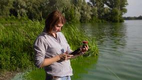A ecologista da mulher adulta examina a amostra de algas verdes e incorpora dados na tabuleta filme