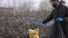Ecologistas amistosos que limpian la basura en el parque metrajes