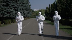 Ecologists team wearing hazmat suits in action running in the park concept of ecology and healthy life - stock video