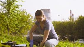 Ecologo della donna che ottiene i campioni delle piante e del suolo vicino alla fabbrica video d archivio