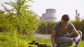 Ecologo della donna che ottiene i campioni delle piante e del suolo vicino alla fabbrica archivi video