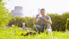 Ecologo della donna che ottiene i campioni di suolo vicino alla fabbrica stock footage