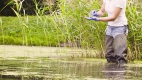 Ecologo della donna che ottiene i sampels delle piante e che misura pH dell'acqua video d archivio