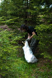 Ecology. Image of a man gathering garbage from a wood during campaign of cleaning forest in Fagaras mountain, Barcaciu shelter Royalty Free Stock Photo
