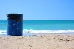 Ecology. Trash barrel on the beach behind waves water sea stock photo