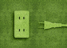 Ecology concept. Green energy concept, Green power cord in electric outlet on a green grassland Stock Image