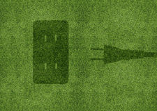 Ecology concept. Green energy concept, Green power cord in electric outlet on a green grassland Royalty Free Stock Photo