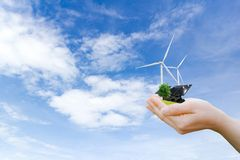Hands holding tree electrical energy clean wind turbine and solar cell the future stock image