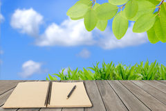 Ecology concept,memo notebook and fresh green field Royalty Free Stock Photos