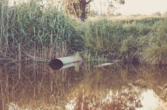 Ecology concept:sewer pipe pour out to lake/water gushing from the sewer to lake stock photography