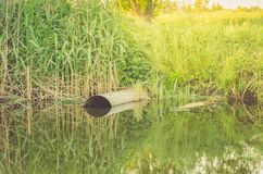 Ecology concept:sewer pipe pour out to river/water gushing from stock photography