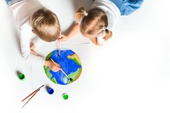 Ecology concept with two prety little kids painting earth on white background. Copy space, top view stock photo