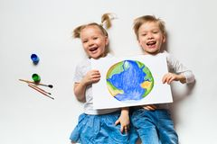 Ecology concept with two prety little kids painting earth on white background. Copy space, top view royalty free stock image