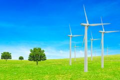 Ecology concept. Windmills, trees,field and beautiful sky. Renewable energy sources.  Stock Images