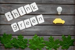 Think green text with car toy, lamp, green maple leaves on wooden background top view. Ecology friendly. Think green text with car toy, lamp, green maple leaves royalty free stock image