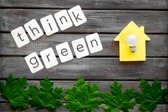Think green text with house toy, lamp, green maple leaves on wooden background top view. Ecology friendly. Think green text with house toy, lamp, green maple stock images