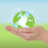 Ecology globe. Female hand with a green globe. Ecology concept Stock Image