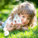 Ecology house in hands. Ecology house in childrens hands against spring green background Royalty Free Stock Images