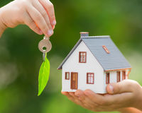 Ecology house and key in hands Stock Photos