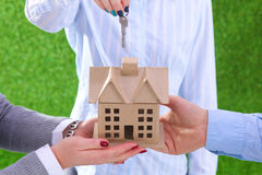 Ecology house and key in hands against green spring background Stock Photos