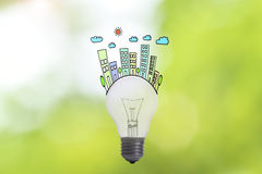 Ecology lightbulb concept house and family on green nature. Royalty Free Stock Photo
