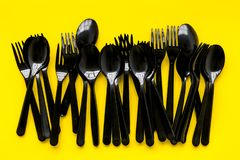 Plastic spoons and forks utilization and the Earth protection concept with flatware on yellow background top view. Ecology. Plastic spoons and forks utilization royalty free stock photography