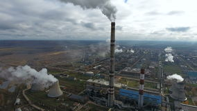 Ecology pollution. Industrial factory pollutes the environment blowing smoke from pipes.