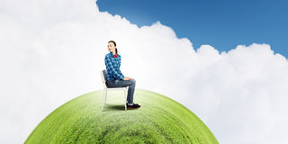 Ecology problem. Young troubled woman sitting in chair on green planet Stock Image
