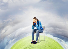 Ecology problem. Young troubled woman sitting in chair on green planet Royalty Free Stock Image
