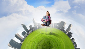 Ecology problem. Young troubled woman sitting in chair on green planet Stock Photography