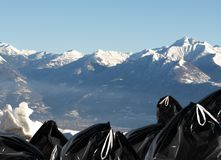 Ecology series -  garbage. Contrast / black garbage and white mountains (swiss mountains Royalty Free Stock Image