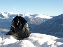 Ecology series -  garbage. Contrast - black garbage and white swiss mountains Royalty Free Stock Image