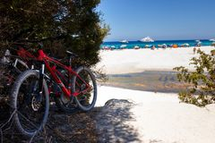 Bicycles taken in rent, parked on a public beach, isolated on seascape background, in summer time, Corsica, France. royalty free stock photography