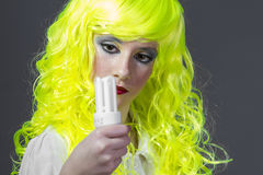 Ecology, teenager with fluorescent yellow wig, carrying a light Stock Photo