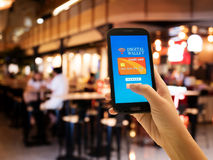 Ecommerce, smart pay, business and technology concept. A digital wallet to pay for goods and services to convenient and fast with blur restaurant background Stock Images