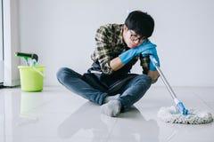 Economía doméstica del marido y concepto de la limpieza, hombre cansado en la frotación azul Imágenes de archivo libres de regalías